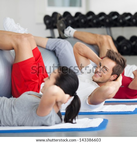 Side view of group with fitness ball practicing crunches in gym - stock photo
