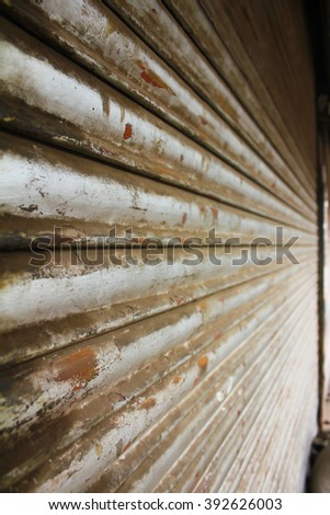 Side view of grunge metallic roller closed shutter of shop - stock photo