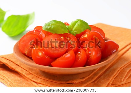 side view of halved cherry tomatoes in the bowl, with basil leaves on the background - stock photo