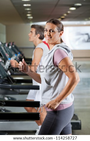 Side view of happy mature woman and man running on treadmill in health club - stock photo