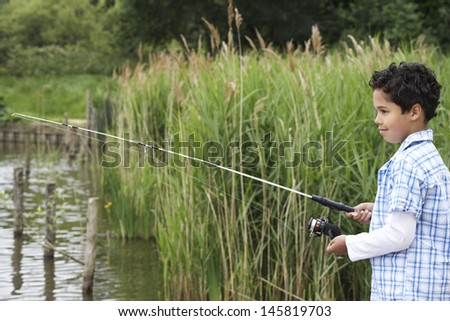 Side view of happy young boy fishing in lake - stock photo