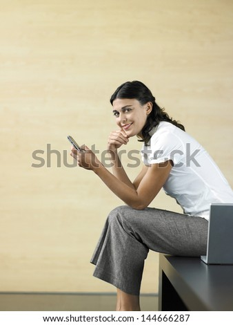 Side view of happy young businesswoman reading text message with laptop on bench in lobby - stock photo