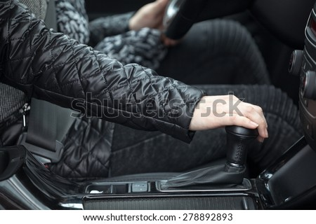 Side view of human hand holding levels of automatic car gearbox, driver seat - stock photo