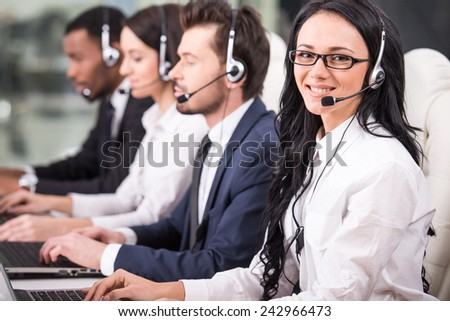 Side view of line of call centre employees are smiling and working on computers. - stock photo