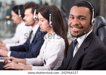 Side view of line of call centre employees are smiling and working on computers. One of them tired and are sleeping. - stock photo
