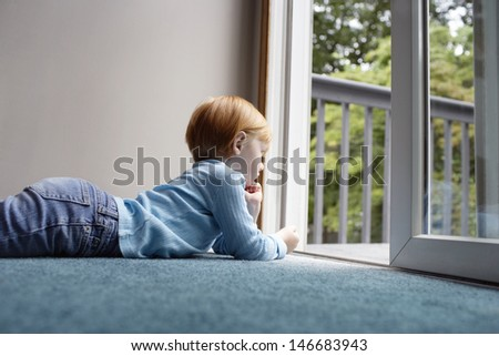 Side view of little girl looking out through balcony while lying on carpet at home - stock photo