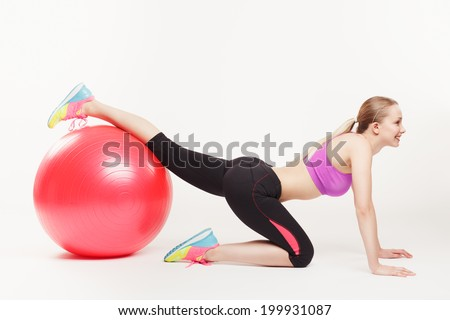 side view of lovely girl doing an exercise with a pink gym ball over white background - stock photo