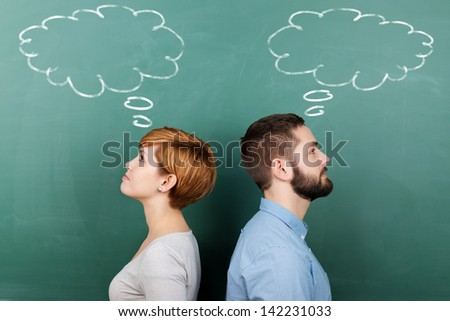 Side view of male and female professors with thought bubble on chalkboard - stock photo