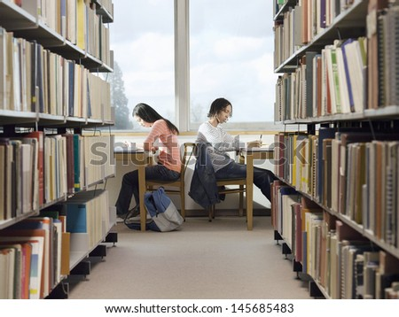 Side view of male and female students doing homework in the library  - stock photo