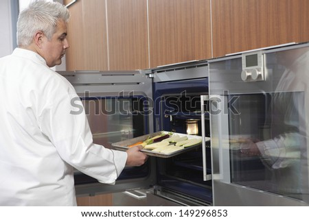 Side view of male chef placing baking tray in oven - stock photo
