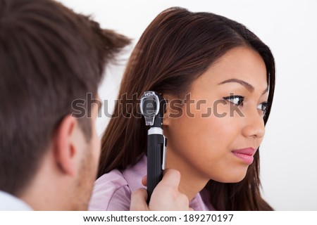 Side view of male doctor examining patient's ear with otoscope in clinic - stock photo