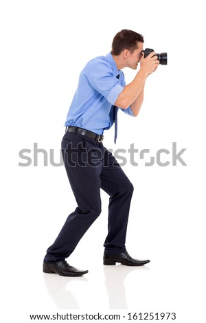 side view of male photographer taking photos on white background - stock photo