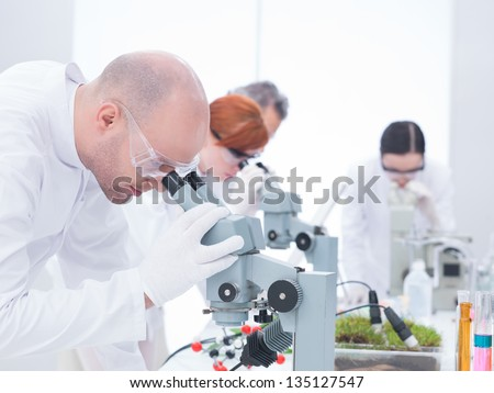 side-view of man in chemistry lab analyzing under microscope and another three researchers on the background - stock photo