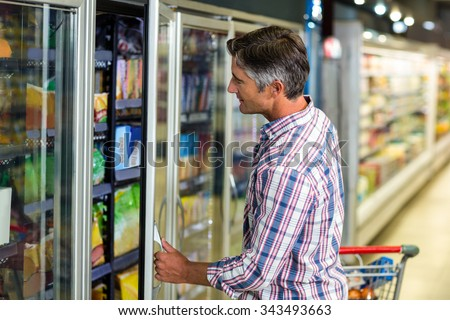 Side view of man opening supermarket fridge - stock photo