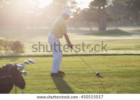 Side view of man playing golf while standing on field - stock photo