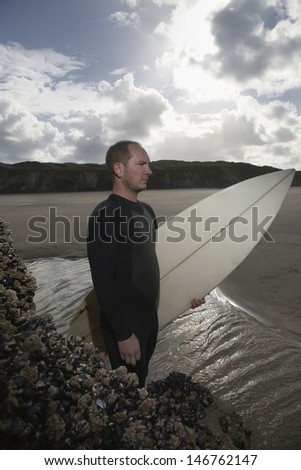 Side view of man with surfboard standing by rock on beach - stock photo