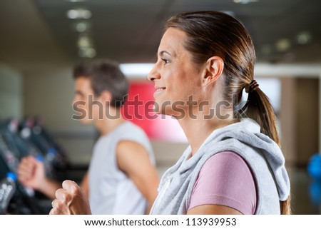 Side view of mature woman and man running on treadmill in health club - stock photo