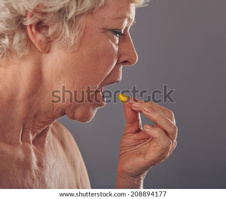 Side view of mature woman talking a tablet against grey background. Time for medication. Old woman having a medicine pill. - stock photo