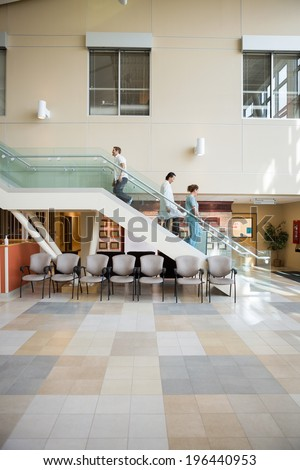 Side view of medical team and patient walking on stairs in hospital - stock photo