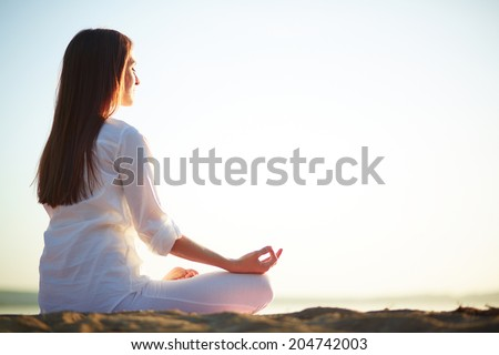Side view of meditating woman sitting in pose of lotus against clear sky outdoors - stock photo