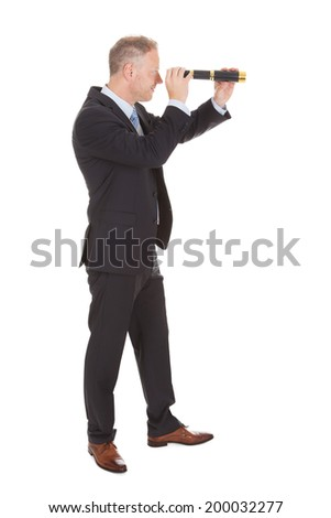 Side view of mid adult businessman looking through handheld telescope over white background - stock photo