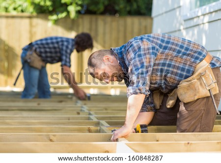 Side view of mid adult carpenters working at construction site - stock photo