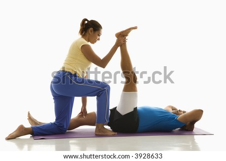 Side view of mid adult multiethnic woman assisting mid adult multi-ethnic man with stretching on exercise mat. - stock photo