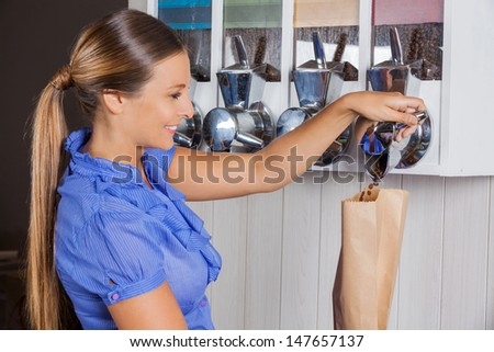 Side view of mid adult woman buying coffee from vending machine in supermarket - stock photo