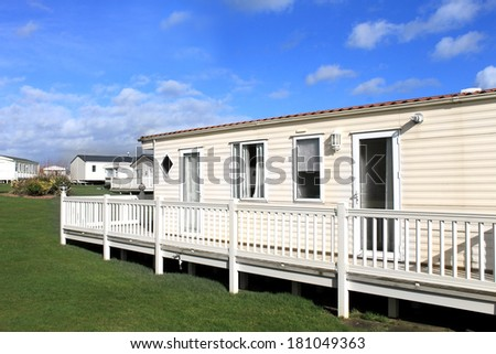 Side view of modern caravan on trailer park with cloudscape background. - stock photo