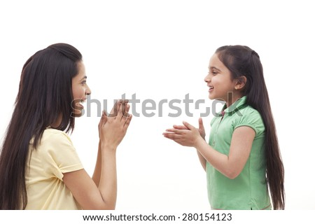 Side view of mother and daughter clapping over white background - stock photo