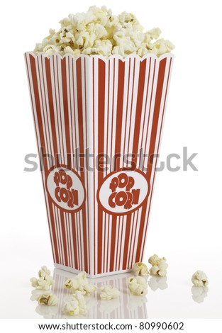 Side view of movie style popcorn box with some spilled out. - stock photo