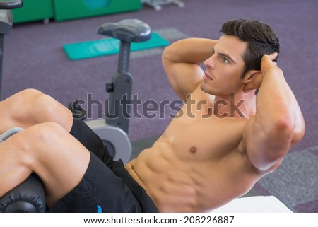 Side view of muscular man doing abdominal crunches in gym - stock photo