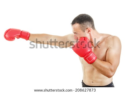 side view of muscular man wearing red boxing gloves and punching on white background - stock photo