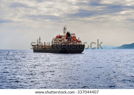 Side view of oil tanker ship exporting fuel and sailing in the sea - stock photo