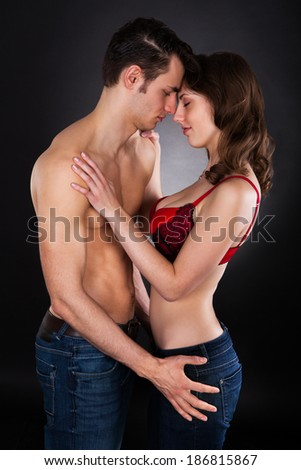 Side view of passionate young couple standing isolated over black background - stock photo