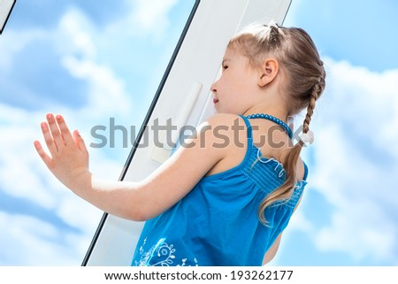Side view of pretty girl behind plastic window glass - stock photo