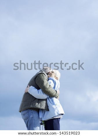Side view of romantic senior couple embracing against cloudy sky - stock photo