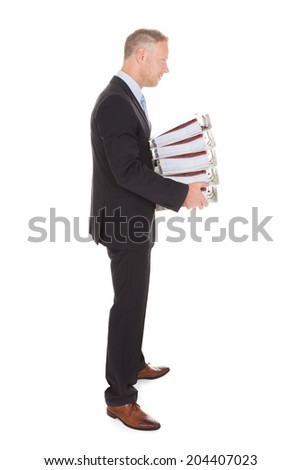 Side view of sad businessman carrying stack of binders over white background - stock photo