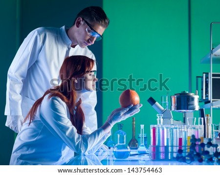 side view of scientists looking at a colorful grapefruit in a laboratory - stock photo