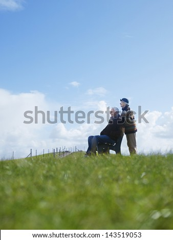 Side view of senior couple relaxing at park - stock photo