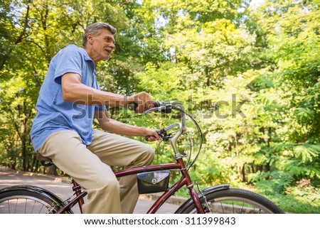 Side view of senior man is riding bicycle in park. - stock photo