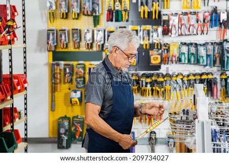 Side view of senior man working in hardware shop - stock photo