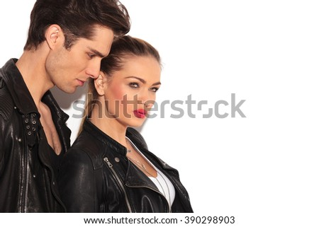 side view of sexy young couple in leather jackets looking away from the camera  - stock photo