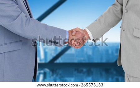 Side view of shaking hands against room with large window looking on city - stock photo