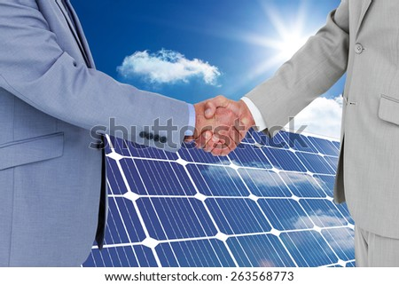 Side view of shaking hands against solar panel reflecting sunlight - stock photo