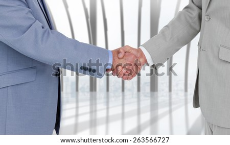 Side view of shaking hands against white room with large window overlooking city - stock photo