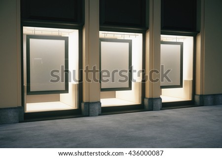 Side view of shop exterior with blank frames in glass showcase at night. Mock up, 3D Rendering - stock photo