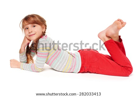Side view of smiling child girl lying on stomach on the floor with crossed legs, over white background  - stock photo