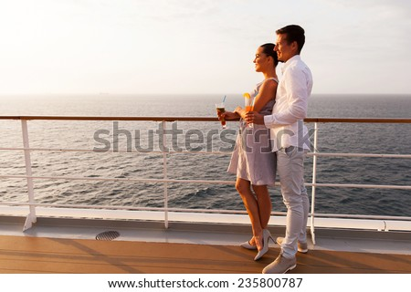 side view of smiling couple having cocktails on cruise ship at sunset - stock photo