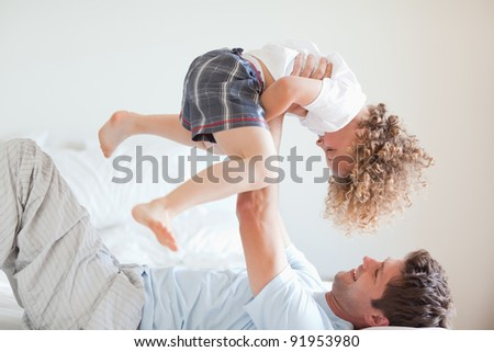 Side view of smiling father lifting his child - stock photo
